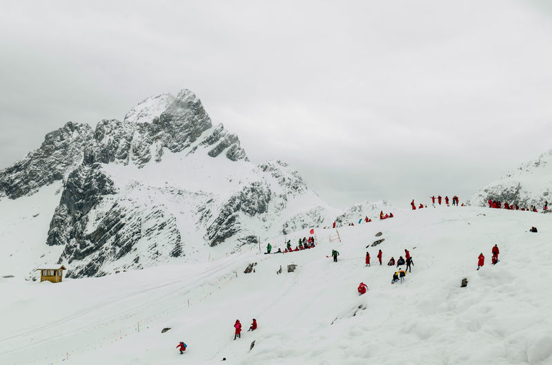 Scenic View Of People Skiing Against Cloudy Sky