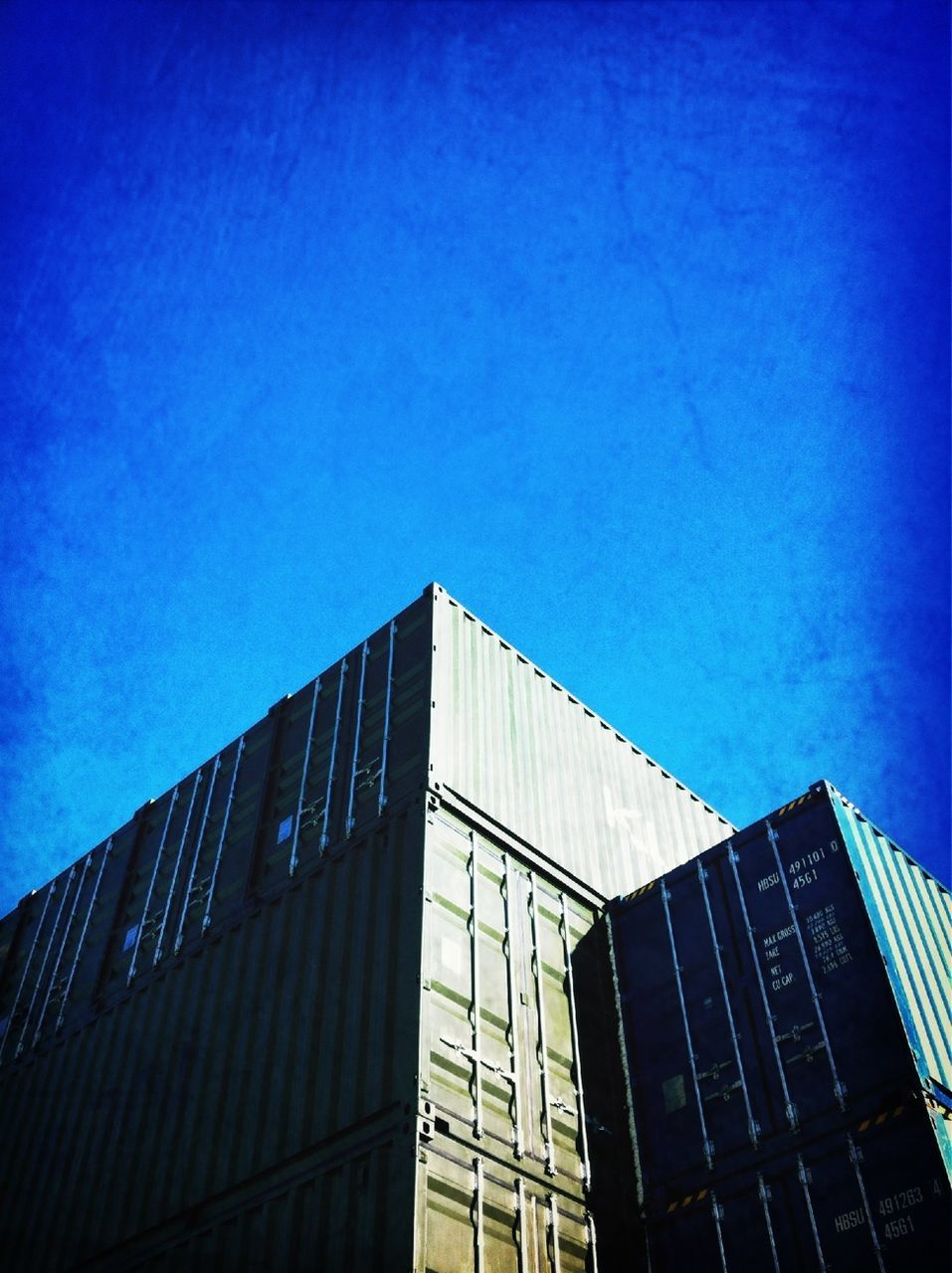 Low angle view of cargo containers against sky