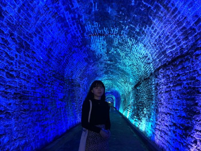 Full length of woman standing in illuminated tunnel