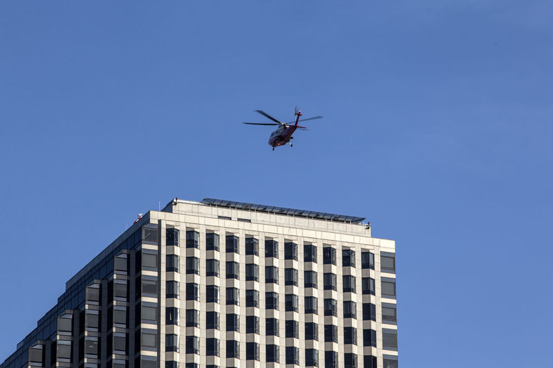 Low Angle View Of Helicopter Flying Over Modern Building Against Blue Sky