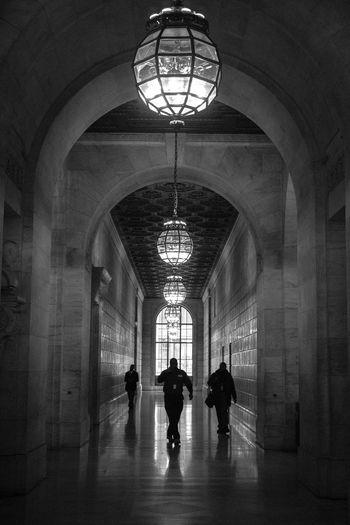 A silhouette of staff at the New York City Public Library in Manhattan, New York City, New York, USA. Arch Architecture Black & White Black And White Black And White Photography Blackandwhite Blackandwhite Photography Built Structure Ceiling Corridor Diminishing Perspective Illuminated Lighting Equipment New York New York City New York Public Library Silhouette Silhouettes