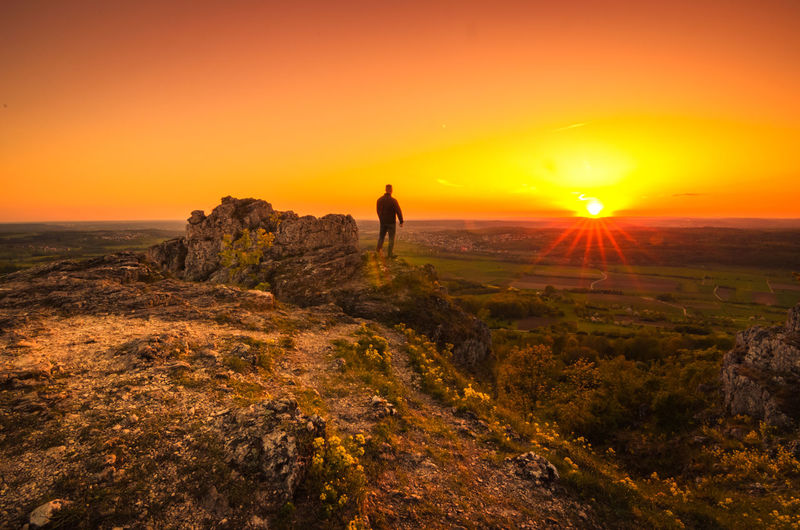 Man standing on rock against orange sky