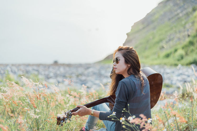 Woman With Guitar Sitting On Field