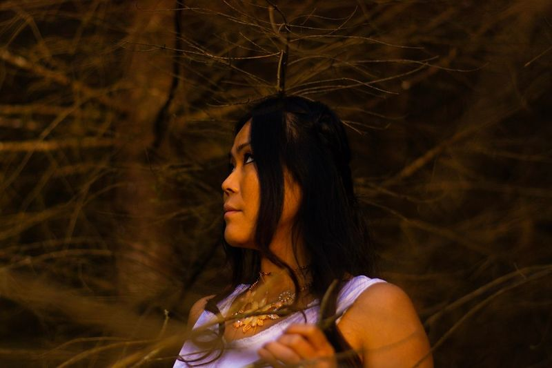 Young woman looking away against trees at night