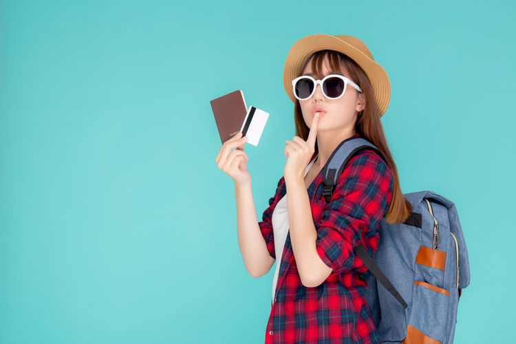 Young woman with backpack holding passport and credit card while standing against blue background