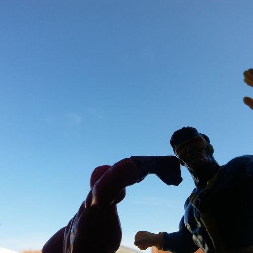Low angle view of people against clear blue sky