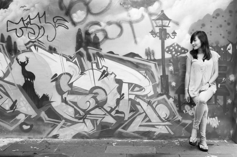 Smiling woman leaning on graffiti over wall