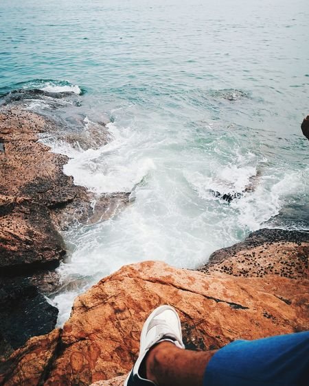 Low section of person on rock by sea