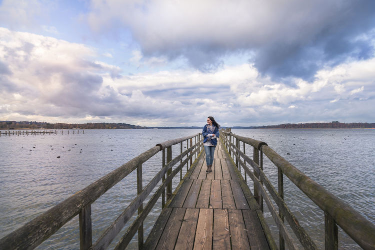 Beautiful young woman smiling and walking alone on a long wooden pontoon, over the lake Chiemsee, enjoying the fresh air and the sunset, in Germany. Chiemsee Winter Wooden Bridge Chiemsee Cloud - Sky Famous Place Footbridge Nature One Person Outdoors Pier Railing Real People Sky Travel Destinations Water Young Woman