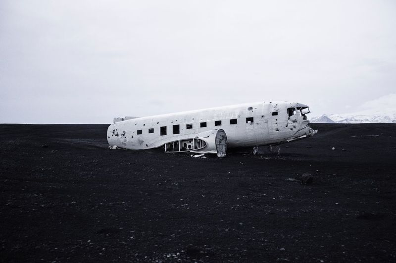 Side view of an abandoned airplane on landscape