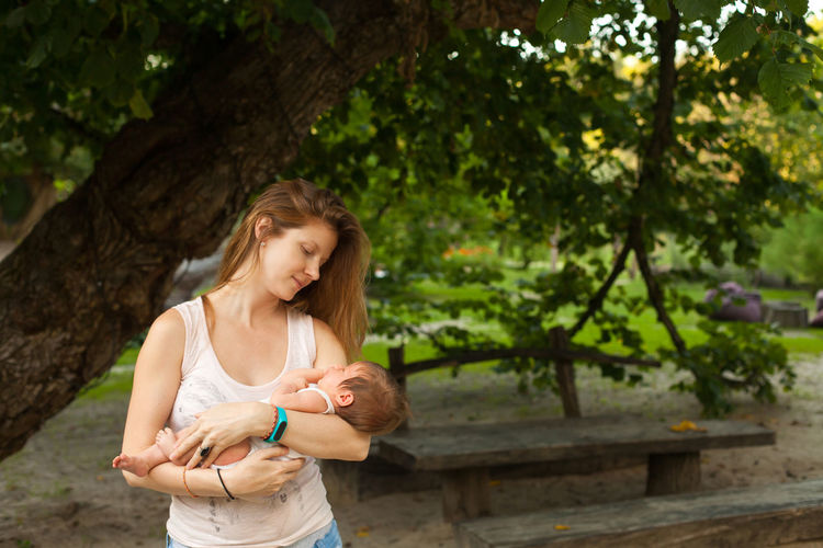 Woman holding baby while standing against tree trunk