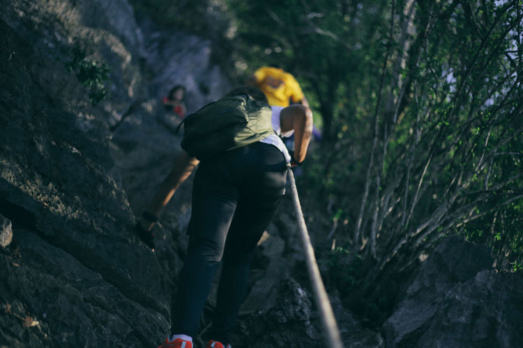 Low angle view of hikers climbing mountain