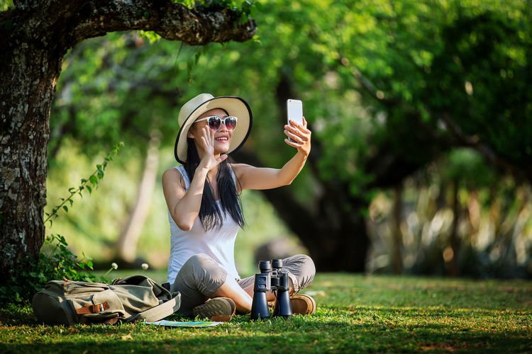 Casual Clothing Communication Fashion Focus On Foreground Glasses Grass Holding Leisure Activity Lifestyles Mobile Phone Nature One Person Outdoors Plant Real People Sitting Smart Phone Sunglasses Tree Wireless Technology Young Adult Young Women