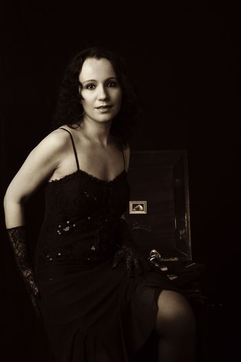 Portrait Of Sensuous Beautiful Woman In Dress Standing By Gramophone Against Black Background
