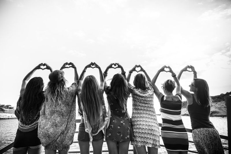 Rear view of friends making heart shape while standing by railing against sky