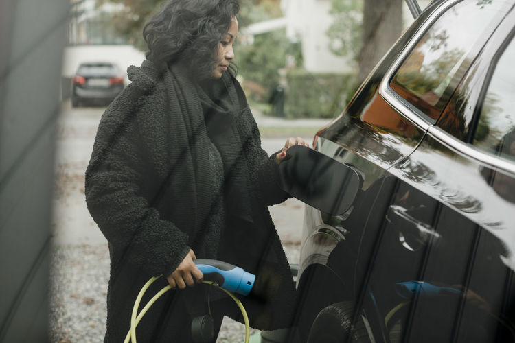 Midsection of woman holding umbrella while standing by car