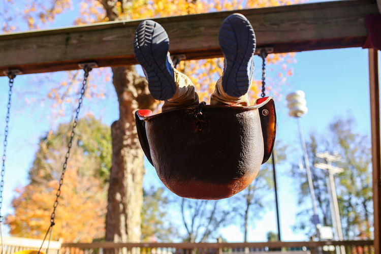Child swinging in swing Sky Wood - Material Low Angle View Close-up Focus On Foreground Day Nature Outdoors Childhood Boy Swinging Swing Playground Fall Autumn Fall Colors Autumn colors Autumn Collection Swingset Playset Playing Child Playing