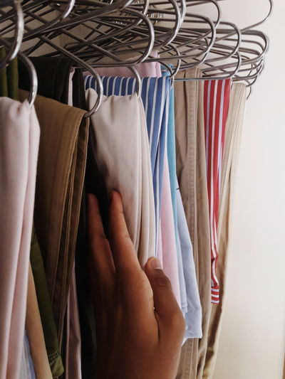 Cropped hand of person choosing clothes hanging on coathangers