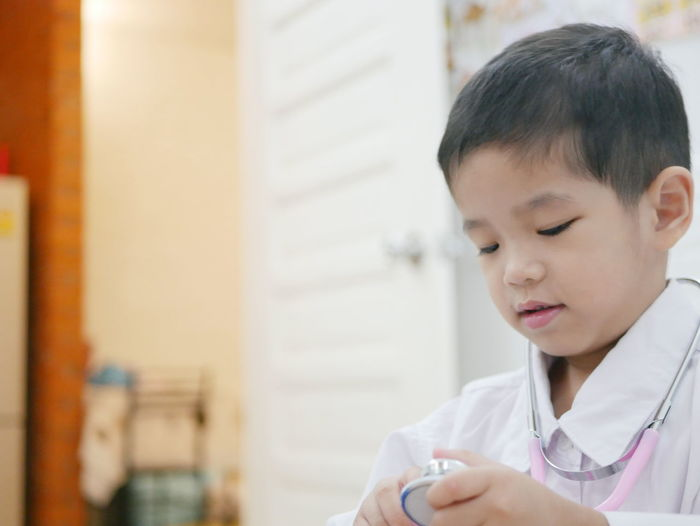 Close-Up Of Boy Holding Stethoscope At Home