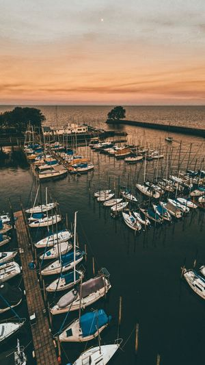 High angle view of fishing boats moored at harbor during sunset