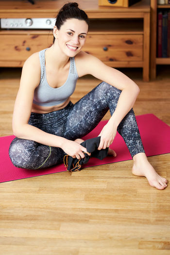 Portrait of happy woman sitting on wooden floor