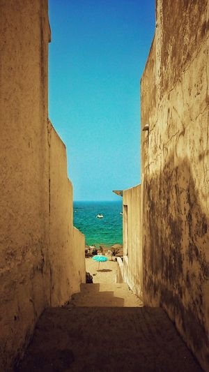 Scenic view of alley leading to sea against clear sky