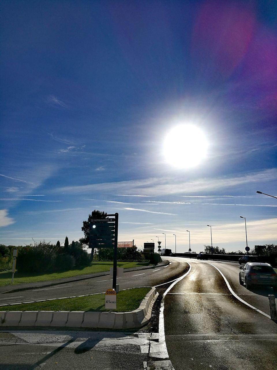 transportation, road, sky, the way forward, street, car, outdoors, sun, sunlight, street light, cloud - sky, no people, tree, day, nature, building exterior, city, architecture