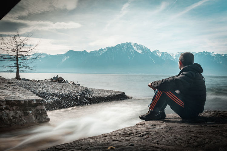 Rear view of man sitting on rock against mountains