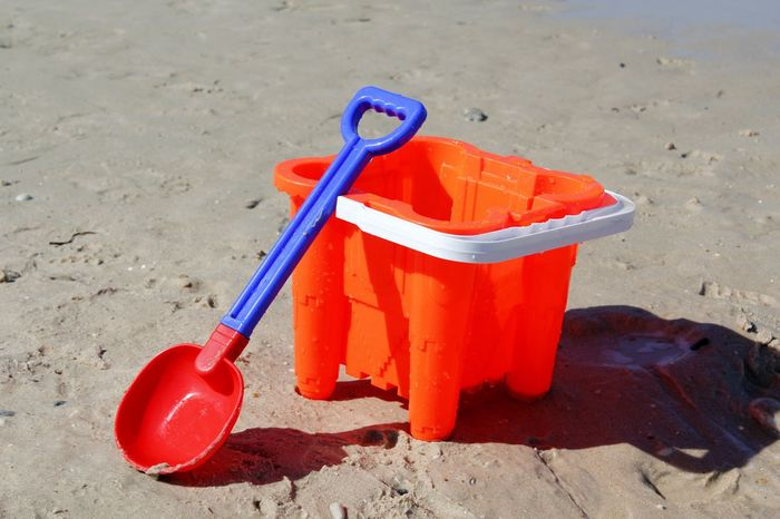 A bucket and spade on the beach Beach Beach Toy Childhood Childs Toy Close-up Day Fun No People Orange Color Outdoors Plastic Red Sand Sand Pail And Shovel Toy