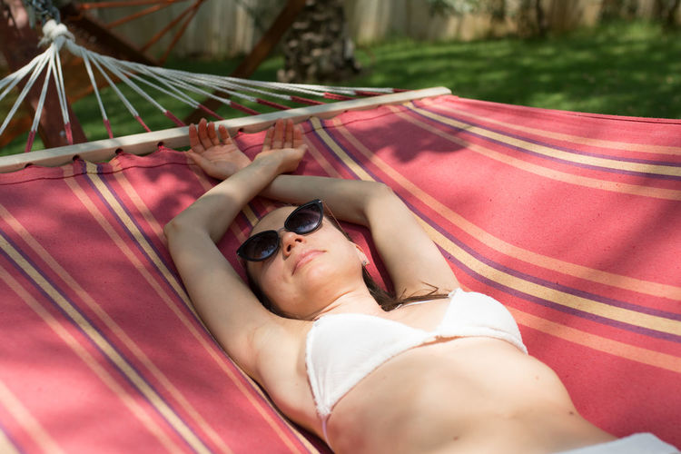Woman Wearing Sunglasses While Relaxing On Hammock