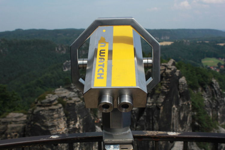 Close-up of yellow train on mountain against sky