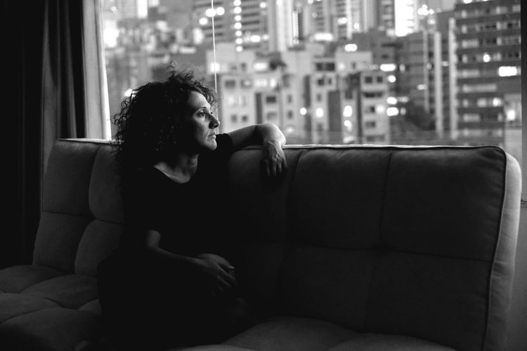 Woman Sitting On Sofa While Looking Through Window In Hotel