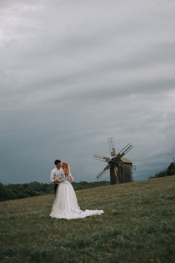 Couple kissing on grass against sky