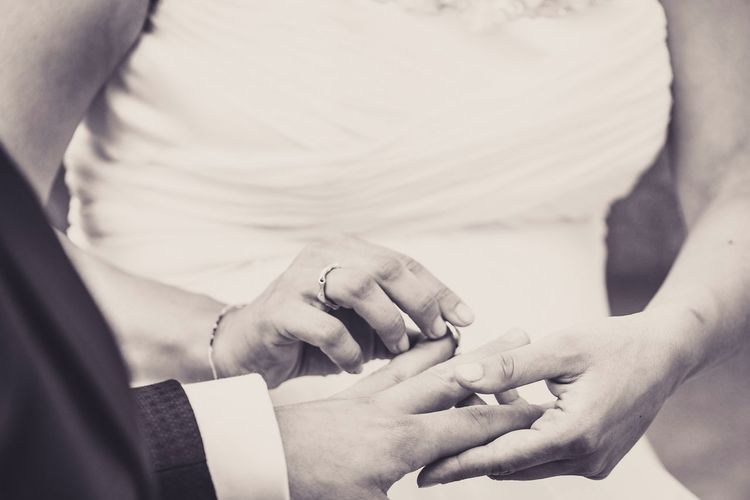 Midsection of bride putting ring in groom finger