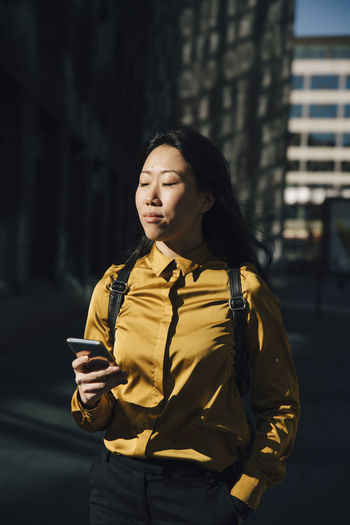 Young woman using phone while standing in city