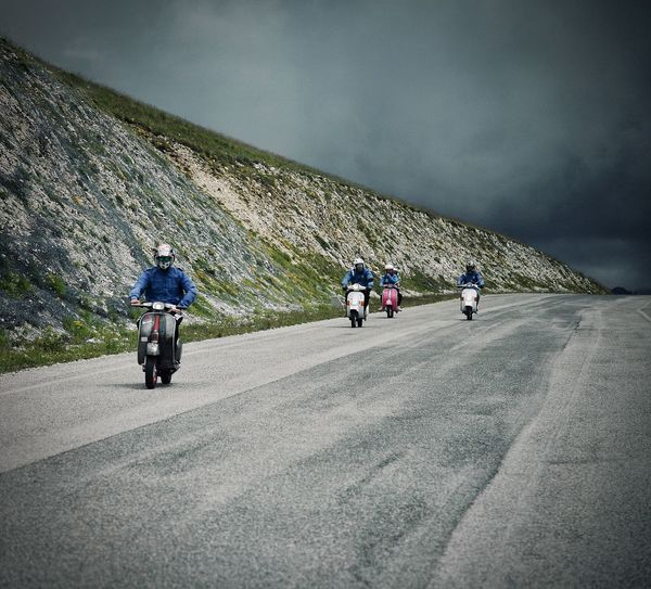 Rear view of people riding motorcycle on road against sky