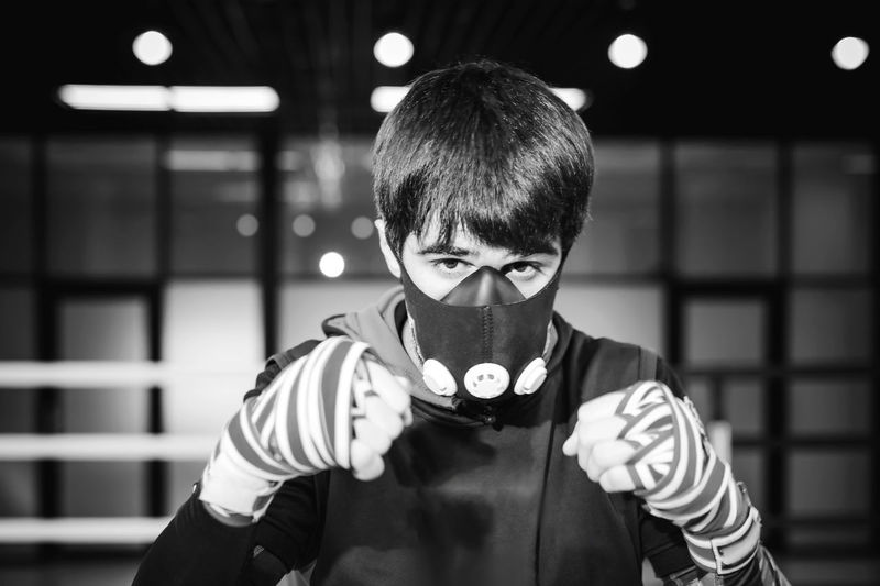 Portrait of man in mask practicing at boxing ring