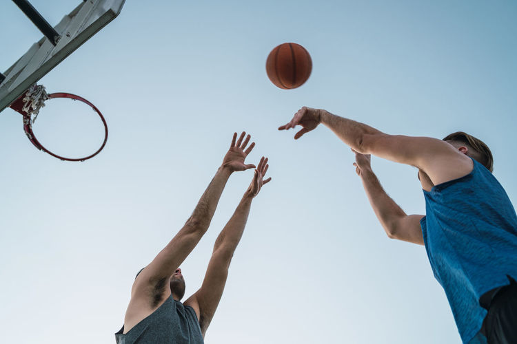 Low angle view of man playing with ball against sky