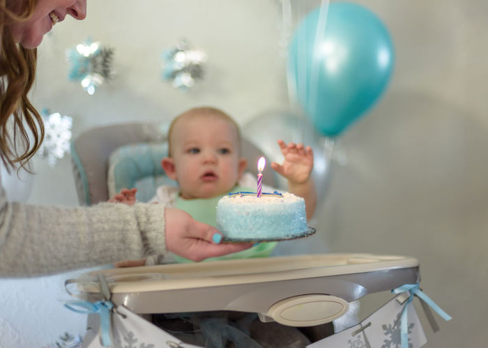 Mother holding birthday cake by baby boy sitting on high chair during birthday party