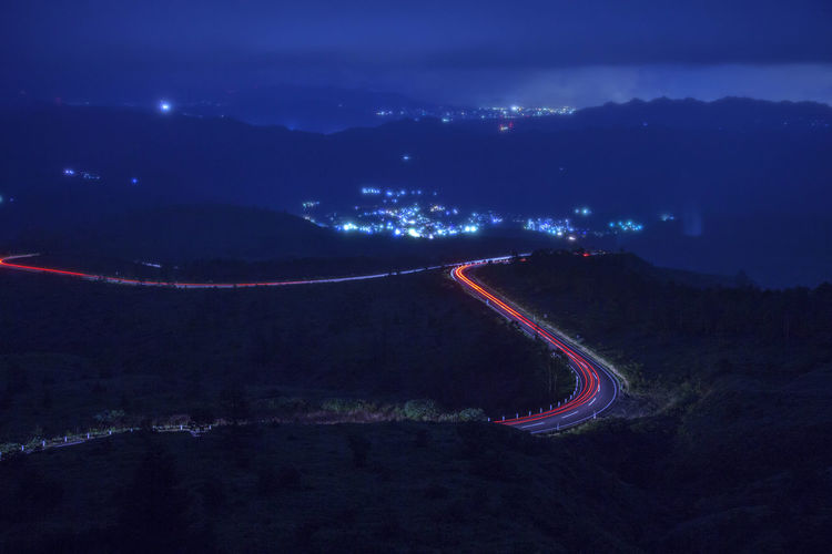 Light trails on road amidst land at night