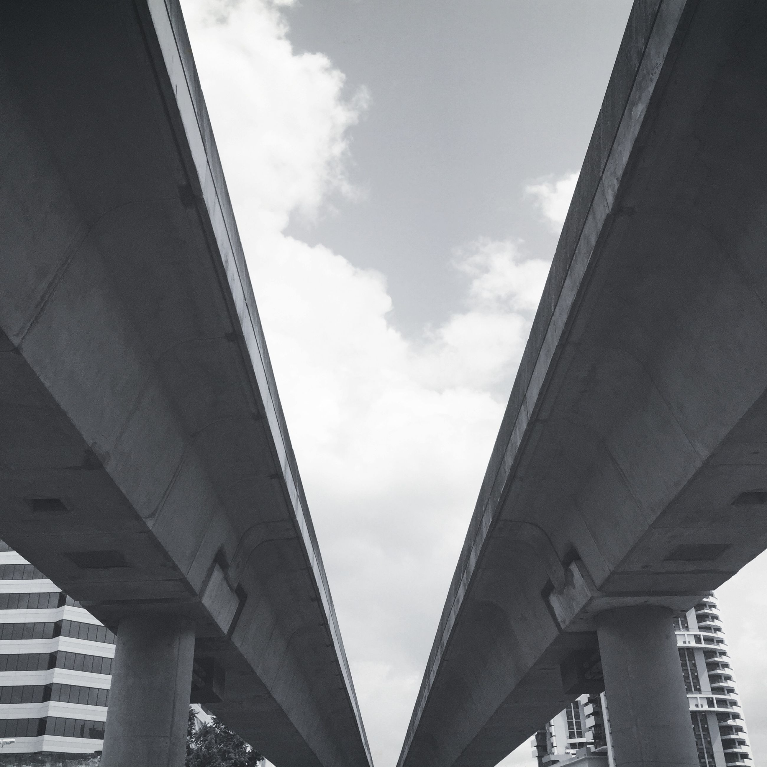 architecture, built structure, low angle view, building exterior, sky, bridge - man made structure, city, connection, engineering, modern, skyscraper, transportation, cloud - sky, day, bridge, outdoors, building, no people, office building, cloud