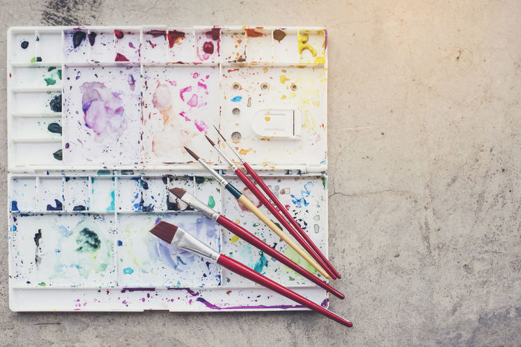 Directly above shot of paintbrushes and palette on table