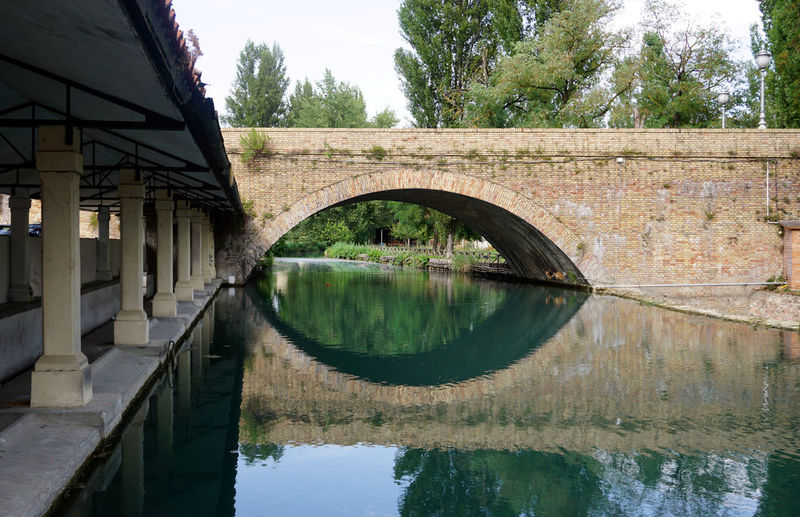 Arch bridge over lake by buildings against sky