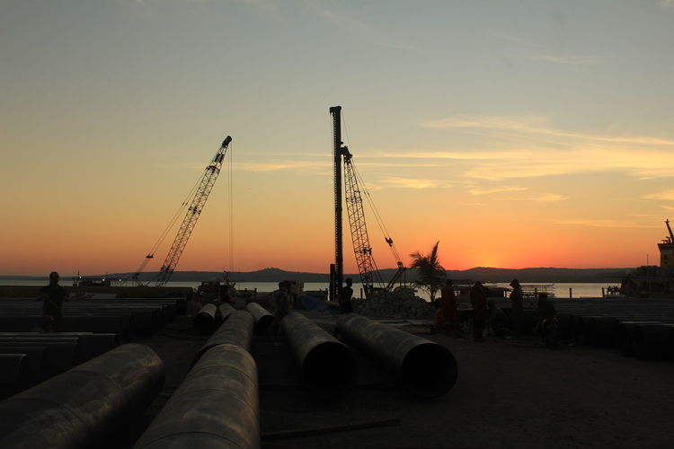 Construction site by sea against sky during sunset