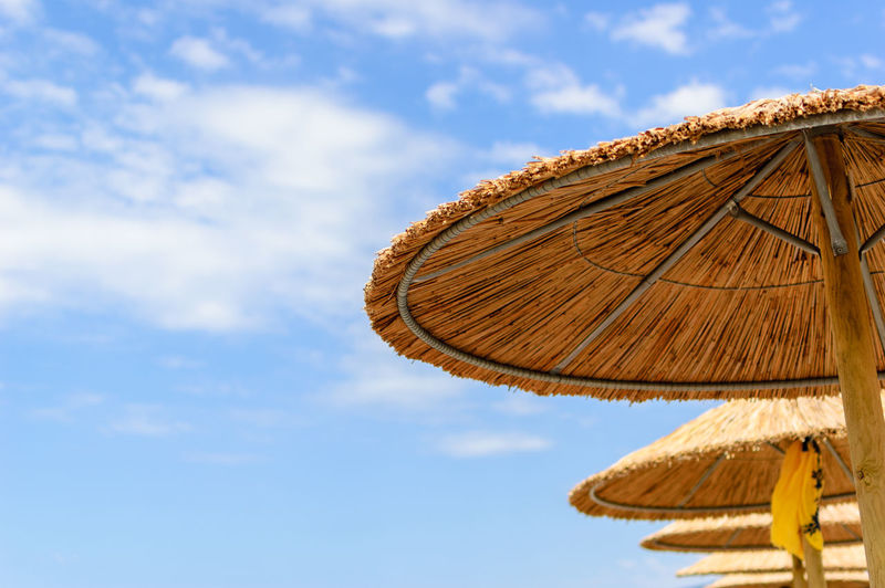 Thatched roof of beach umbrellas against sky