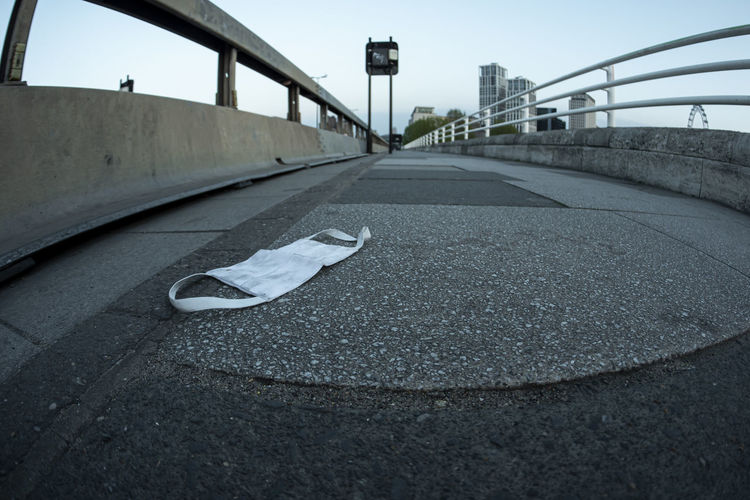 Surface level of road by bridge in city against sky