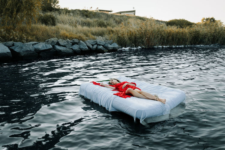Young woman sleeping on bed in lake