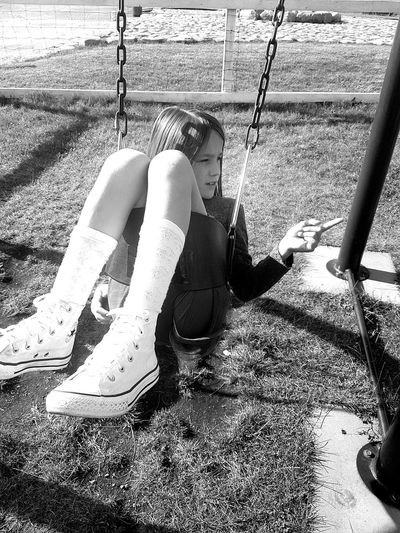 High angle view of girl pointing while sitting on swing in playground