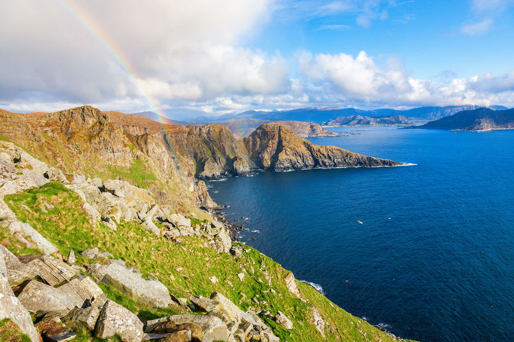 Awesome view at a rocky coastline by the sea and with a rainbow