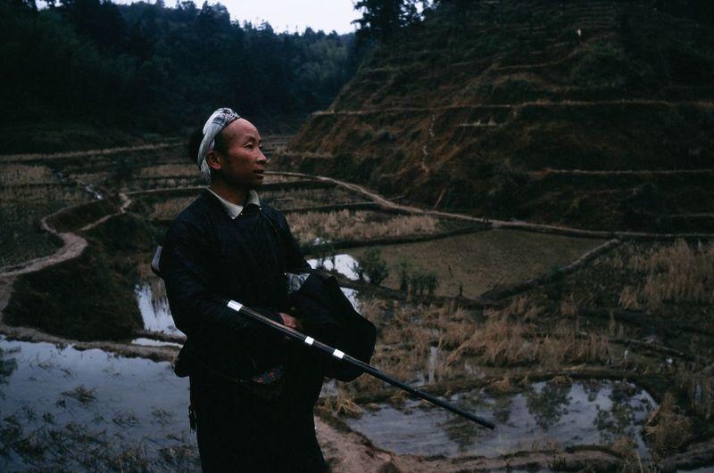 Man holding umbrella standing on mountain